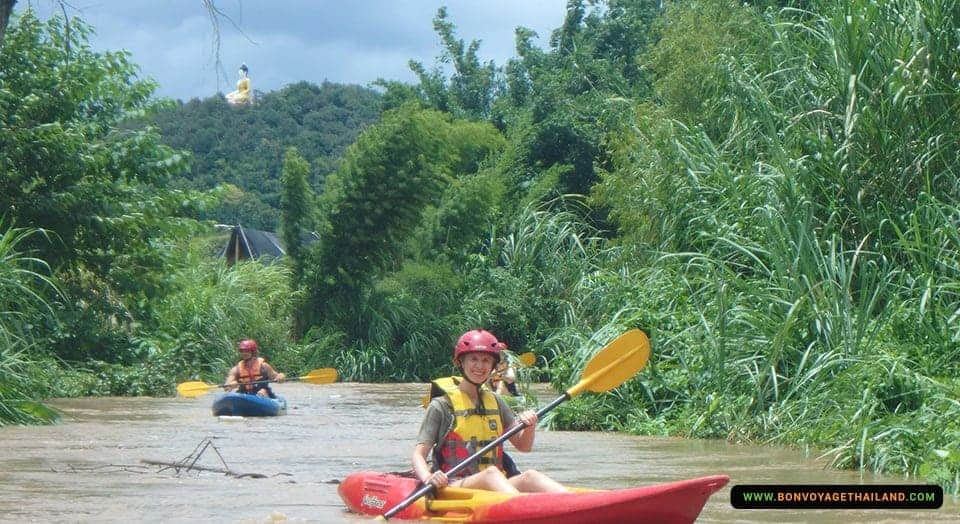 woman kayaking through chiang dao jungle river