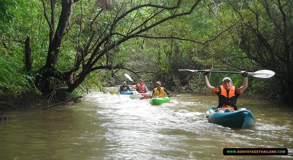 group of people kayaking through chiang dao jungle river