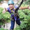 young man giving 2 thumbs up while descending from treetop