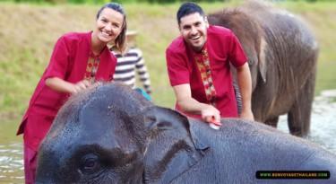 man and woman bathing elephant