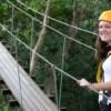 smiling woman walking on wooden sky bridge