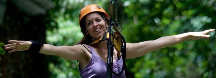 woman ziplining through jungle