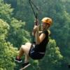 woman ziplining at jungle flight while giving a thumb-up