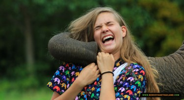 close up of young woman laughing and playing with elephant