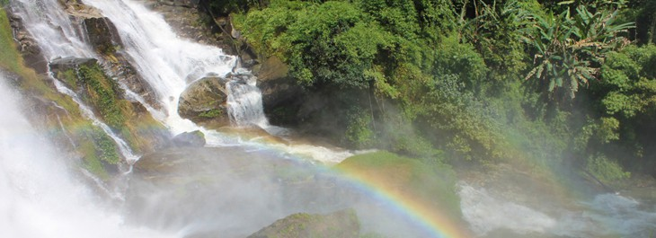 cascading waterfall with rainbow