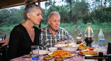 man and woman enjoying traditional thai dinner on ping river cruise