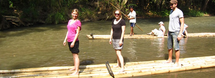 group of people bamboo rafting along mae wang river
