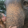 young lady with mud on face kissing an elephant