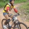 young woman mountain biking on a dirt road
