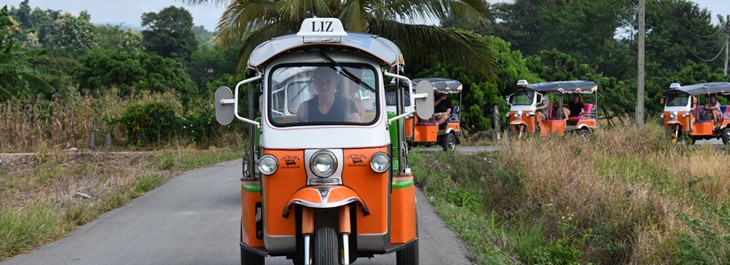 a convoy of tuk-tuks in Thai countryside