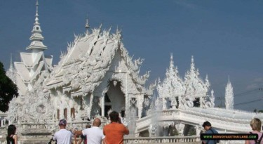 tourists taking photos of white temple or wat rong khun