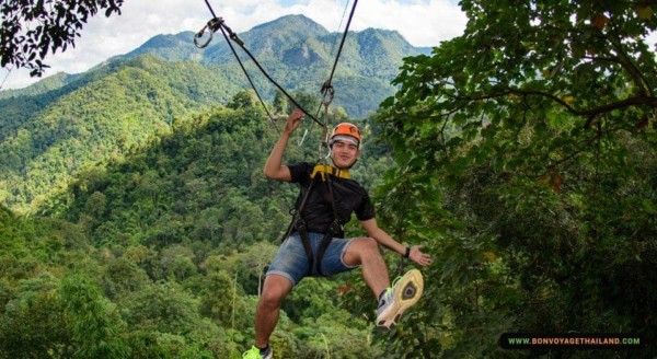 man ziplining through jungle