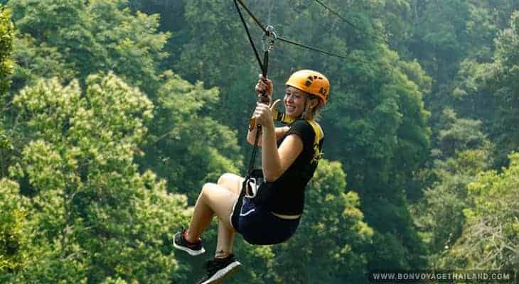 young woman ziplining through jungle