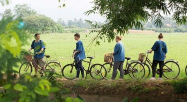 men and women walking their bicycles along rice paddy