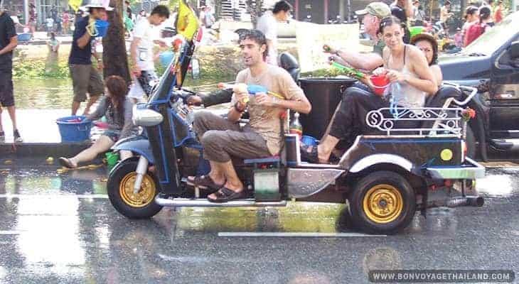 water gun fighting in tuk tuk along the road during songkran festival in chiang mai