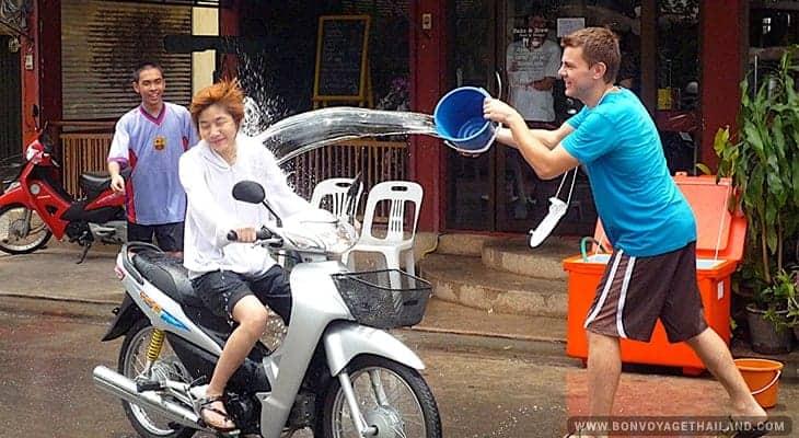 man splashing water on woman on a motorbike during songkran festival in chiang mai