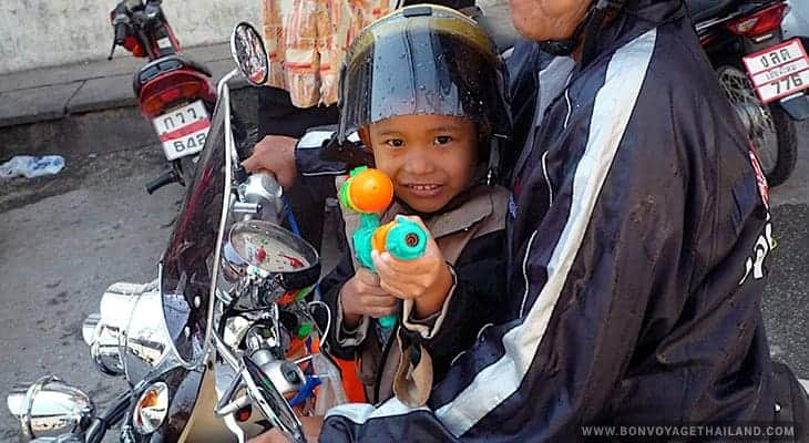 young boy playing with water gun during songkran festival