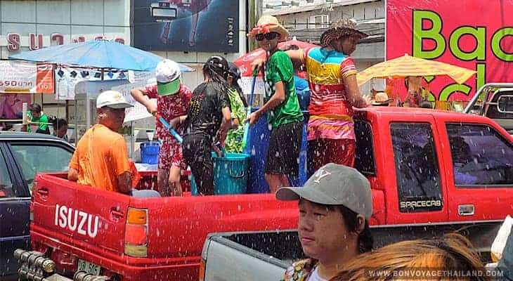 group of people in back of truck enjoy water fights during songkran festival in chiang mai