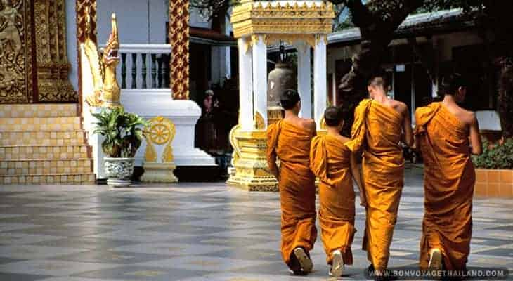 a group of buddhist monks walking in temple