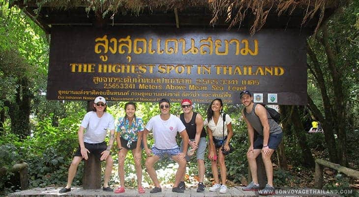 group of people posing for a photo at highest point in thailand