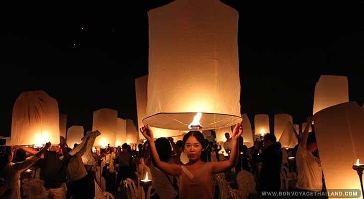 woman preparing to release lit paper lantern into the sky during yeepeng festival