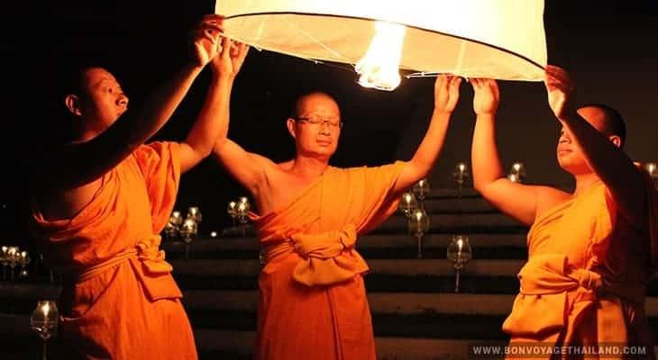 monks releasing lit lantern during yeepeng festival